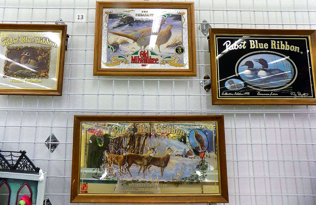 Collectible beer signs including three Pabst Blue Ribbon and one Old Milwaukee.