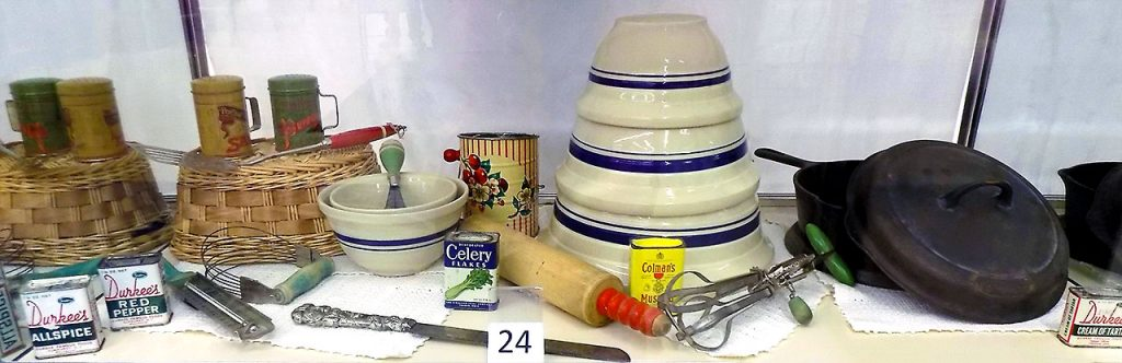 Vintage kitchen utensils including a Griswold cast iron frying pan and a set of mixing bowls.