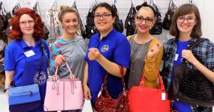 SVDP workers showing off their purses in the purse section of St. Vincent de Paul Fond du Lac.